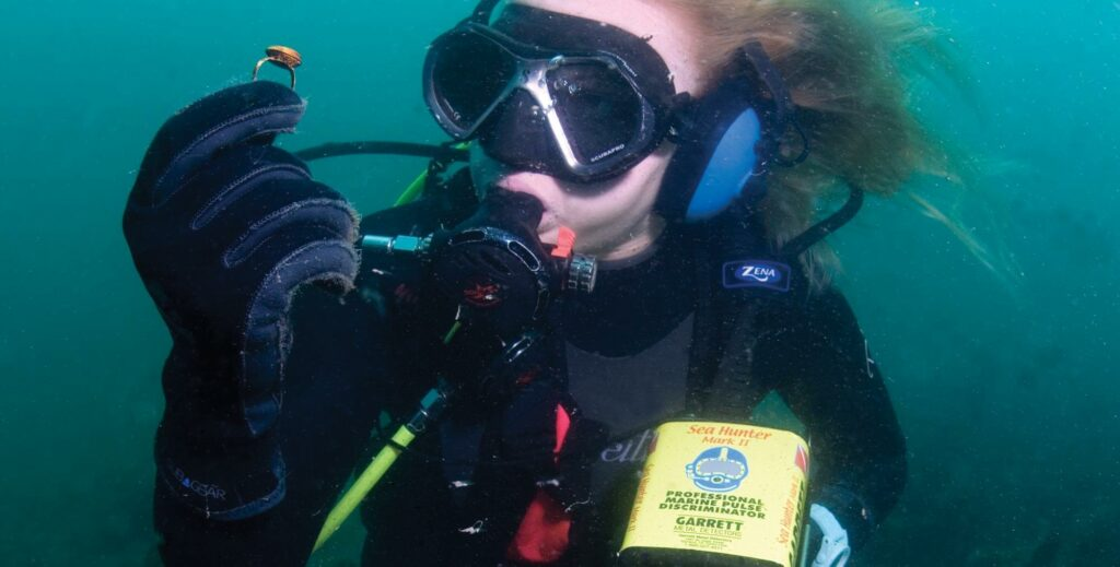 Diver uses an underwater metal detector to find valuable items