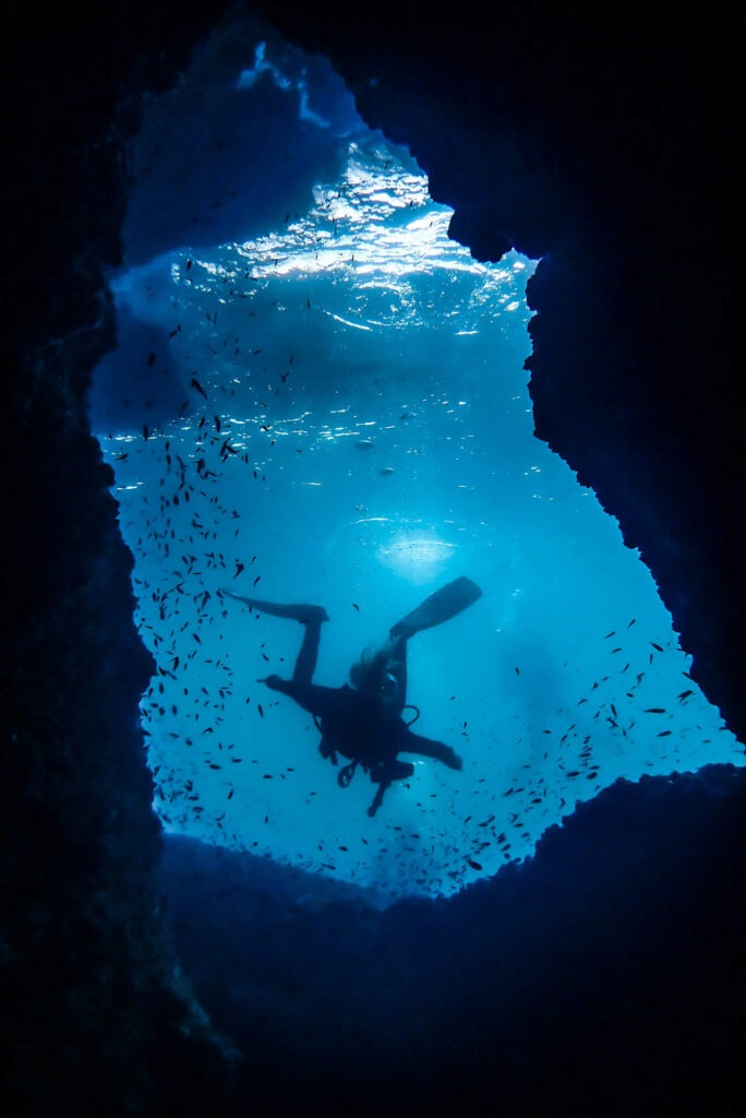 A scuba diver exiting a swim-through at Malong dive site