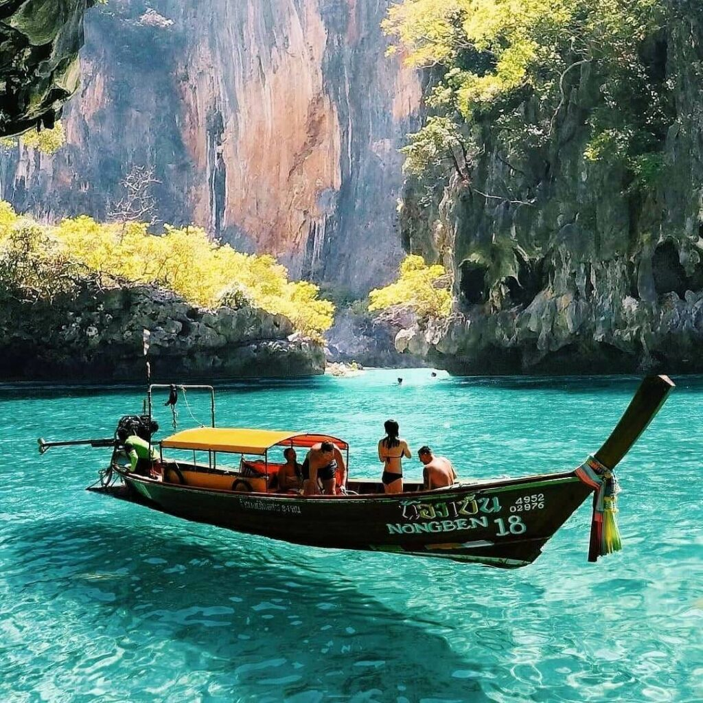 Tourists visit the crystal clear waters of Pileh Lagoon on a longtail