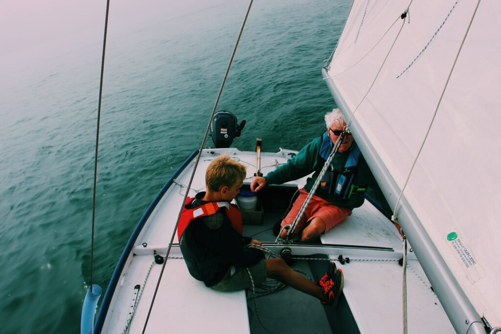 A man and his son on a sailboat wearing lifejackets