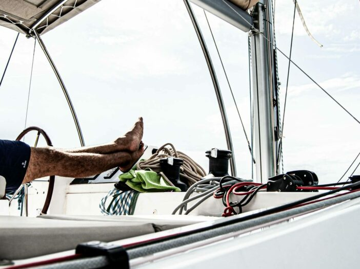 A man puts his feet up while relaxing on his boat